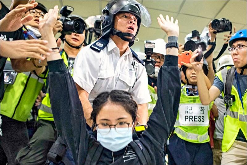 一名女子在警方逐層追捕示威者時高舉雙手,證明她手無寸鐵。 (法新社)