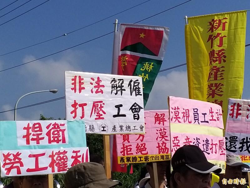 台灣富美家公司工會成員今早頂著大太陽在大門口拉白布條,抗議公司打壓工會,逕自調降勞動條件不利益的變更,不當解僱工會理事長,甚至廠長放話「就是要消滅工會」。(記者廖雪茹攝)