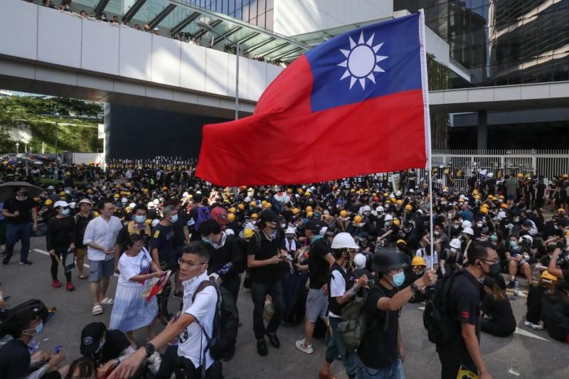 民調顯示,港人贊成台灣獨立的比率大幅上升。圖為香港反送中遊行中出現高舉中華民國國旗的畫面。(歐新社)