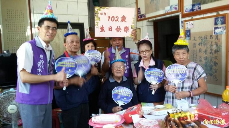 新竹地區102歲人瑞老榮民鄧永興(圖中坐立者),16日過102歲生日,每天都深蹲練腿力,生活沒煩惱的他,還會種菜,雖獨居,卻怡然自得。(記者洪美秀攝)