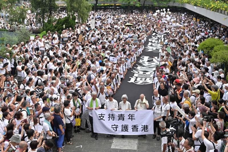 今日香港市民發起的「香港銀髮族靜默遊行」,吸引了上千名銀髮族上街重申五大訴求。(法新社)