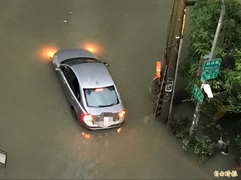 水淹半車身高,試圖闖越卻拋錨。(記者洪臣宏攝)