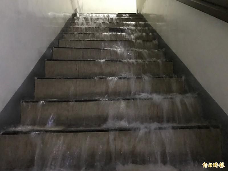 階梯瀑布水勢不斷朝地下停車場宣洩。(記者洪臣宏攝)