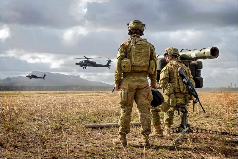 兩架美國陸軍阿帕契攻擊直升機正在澳洲昆士蘭一處訓練區低飛,澳洲陸軍兩名軍人緊盯,其中一人操作RBS 70便攜式防空飛彈。(歐新社)