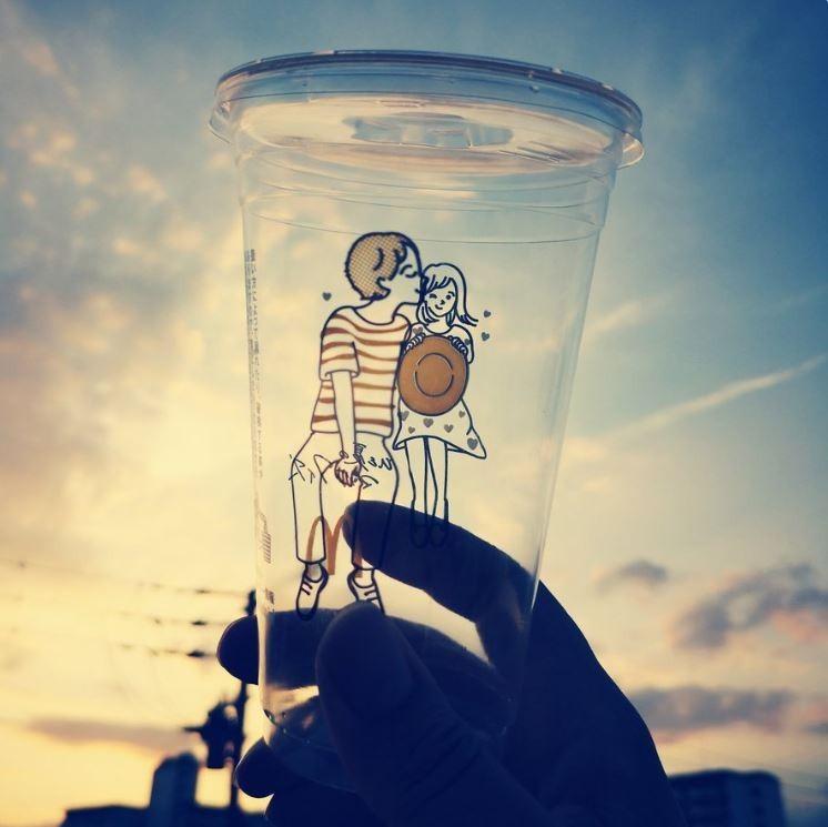 日本麥當勞最近推出夏季限定飲料,在裝飲料的杯身上大搞創意,透明杯身在兩端畫了一男一女,只要旋轉杯身,就能讓小情侶做出親吻等親密動作。(擷取自日本網友推特)