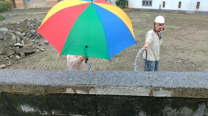 牆內工人發現記者在外拍攝,以雨傘遮臉阻擋。(民眾提供)