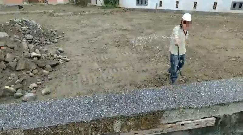 有媒體站在圍籬外拍攝時,牆內工人灑水不慎噴到媒體。(圖擷取自民眾提供影片)
