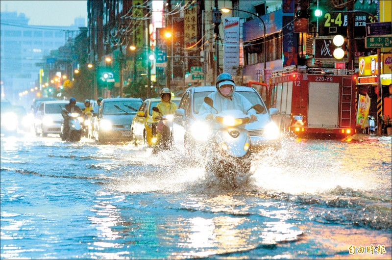高雄市區昨天傍晚降下雷陣雨,超大雨勢讓許多路面積水,車輛拋錨動彈不得,民眾怨聲載道。(記者張忠義攝)