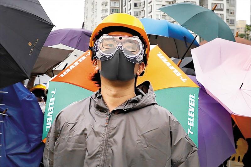 律師表示,衝擊香港立法會的示威者,在申請延長居留台灣有技術上的困難,因為當時多數人都戴上口罩。圖為香港抗議民眾戴上口罩及頭盔,在警局總部前示威。(美聯社檔案照)