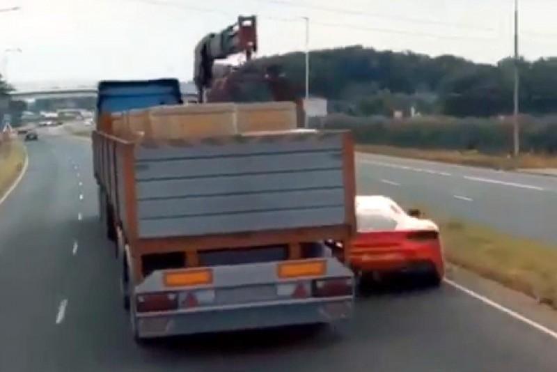 1部紅色跑車從大卡車車底右側穿越而出情形。(記者謝介裕翻攝)