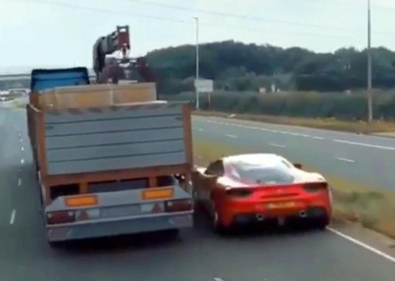 1部紅色跑車毫髮未傷從大卡車車底右側穿越而出,令人嘖嘖稱奇。(記者謝介裕翻攝)