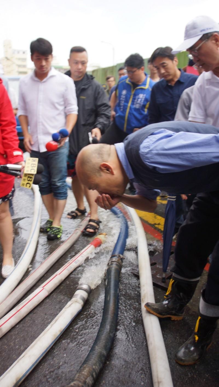 韓國瑜到地下室進水的「裕藏富邑大廈」勘災時,第一動作竟用雙手捧起水來聞。怪異的舉動引起網友熱議。(中央社)