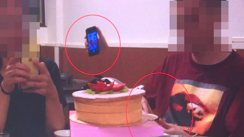 餐桌上的兩人都忙著滑手機,照片卻憑空多出一支拿手機的手。(記者王秀亭翻攝)