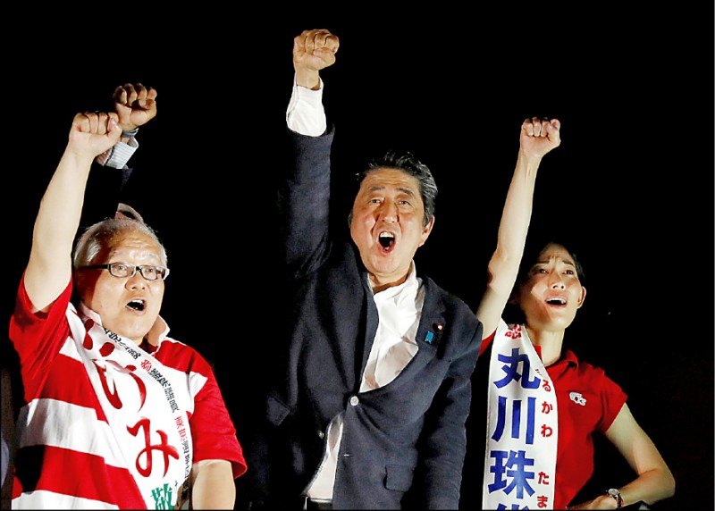 日本參議院21日舉行改選,首相安倍晉三按慣例在秋葉原舉辦選前之夜,支持者從下午就開始聚集;晚間安倍(中)登上宣傳車演說,與候選人一同振臂高呼。(路透)