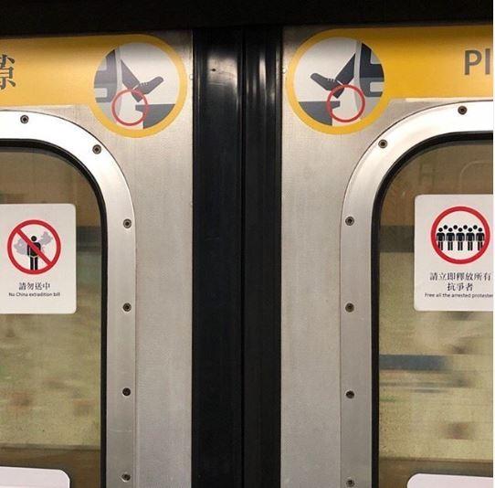 香港「反送中」運動仍持續進行,有香港民眾眼尖發現地鐵上的告示標籤「有異樣」,與原先常見的「請勿飲食」告示相似,上頭卻變成了「請勿送中」等字樣。(圖擷取自IG「midnight_glue」)