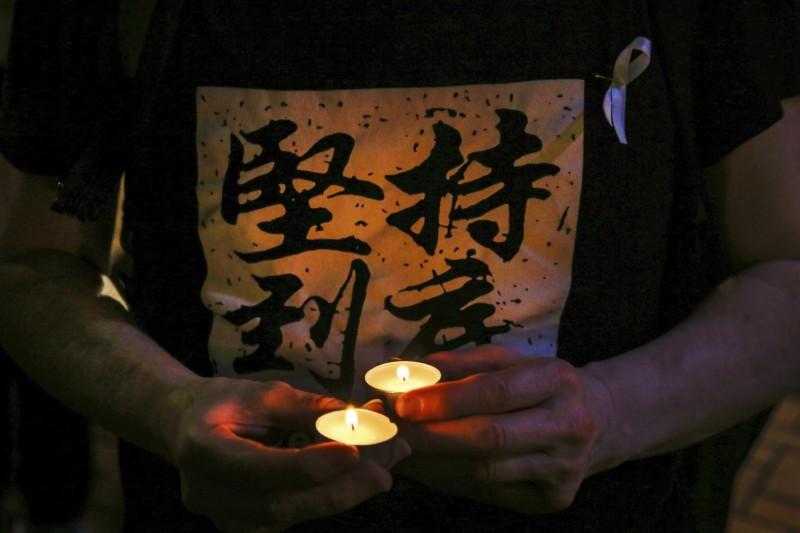香港社福界發起遊行,呼籲政府應該正面回應民間訴求,不應一味希望社工處理社會情緒問題。圖為日前香港民眾為反送中墜樓死者祈福情形。(美聯社)