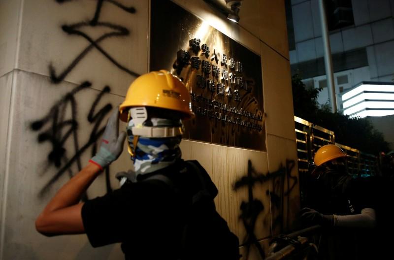 香港部分示威民眾21日晚間抵達中聯辦,在外牆噴上「一國兩制」、「反送中」、「支聯辦」等字眼。(路透)