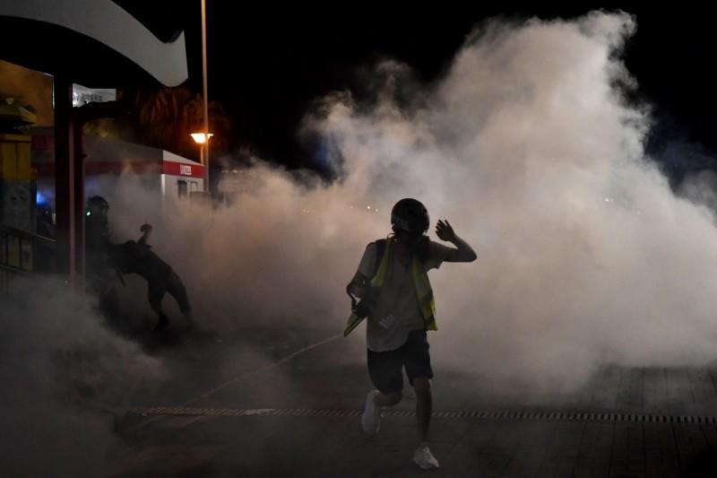 警方於信德中心外發射大量催淚彈,並以警棍追打示威者。(法新社)