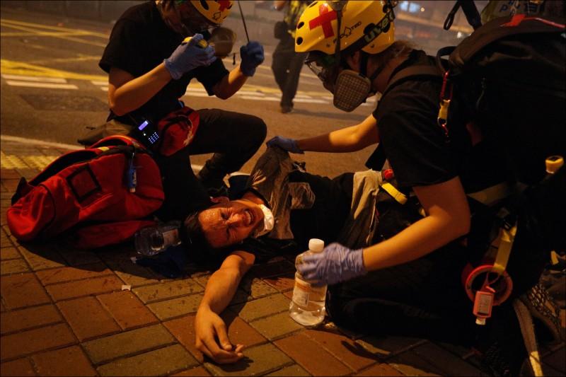 香港示威者中了警察發射的催淚彈,痛苦倒地。(美聯社)