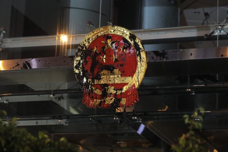 香港反送中群眾昨晚向中聯辦大樓外的中國國徽表達不滿。(法新社)