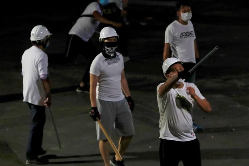 圖為香港元朗21日晚間出現的白衣人士,手持木棒、藤條,攻擊反送中示威者。(路透)