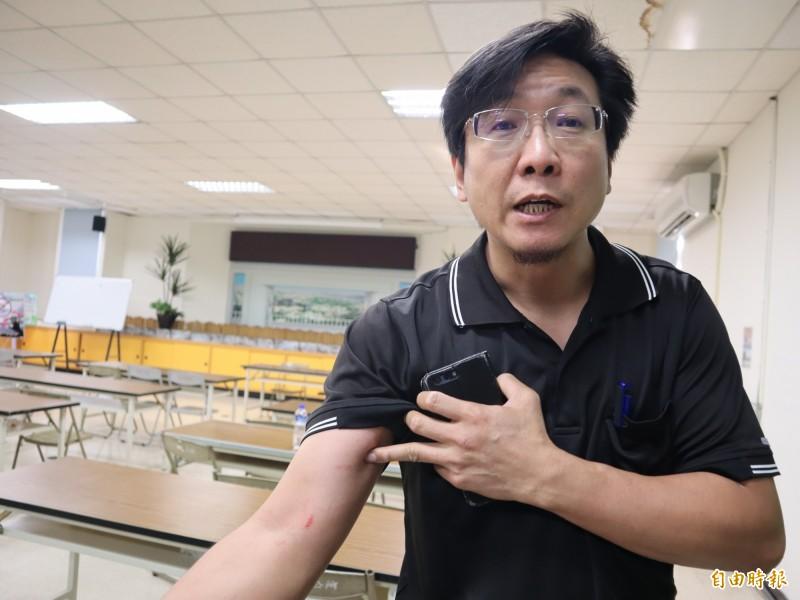 東豐快速道路二階環評說明會豐原場,石岡居民賴俊宏因激動踢桌被員警拖出會場,手臂被抓傷。(記者歐素美攝)