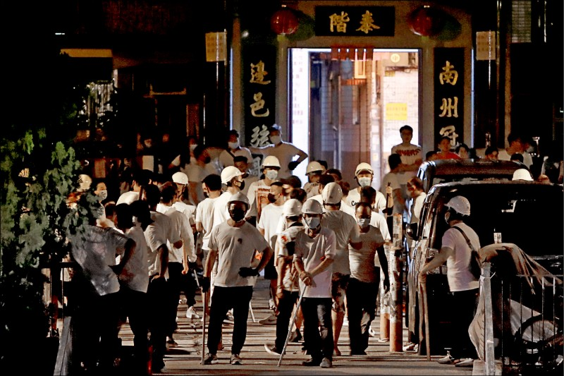 元朗西鐵站二十一日驚傳白衣人糾眾襲擊乘客,造成「反送中」示威者等四十五人受傷。圖為一群白衣男子戴著頭盔及口罩,手持棍棒於二十二日現身元朗街頭。(路透)