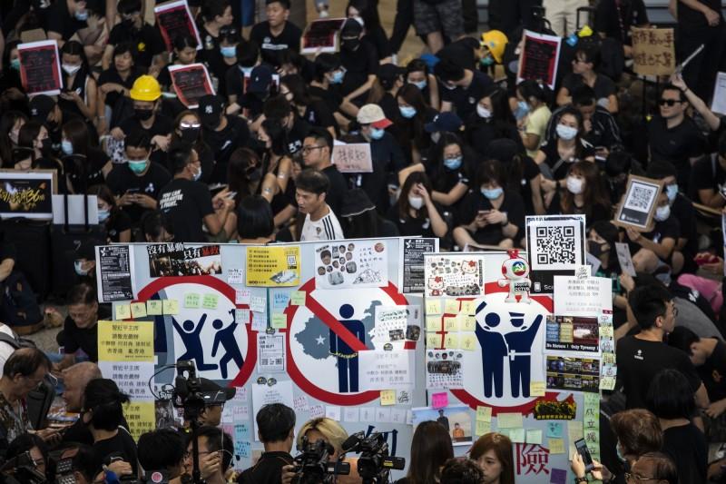 香港民眾和航空業人員今天(26日)聚集在香港國際機場重申反送中5大訴求。(彭博)