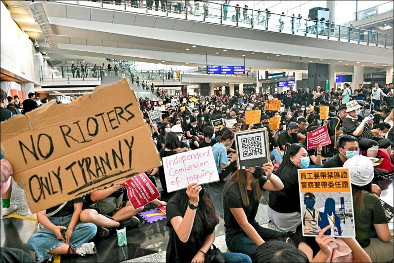 香港赤鱲角機場內的數千名示威者,廿六日在接機大廳靜坐抗議元朗暴力事件。(法新社)