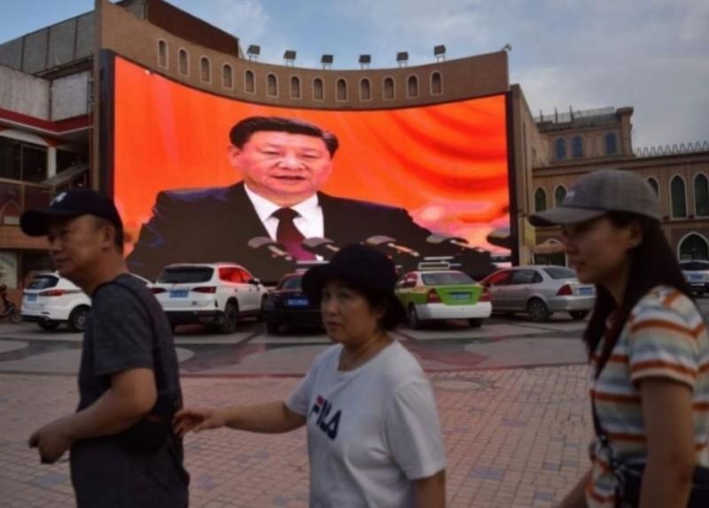 中國國家主席習近平發表講話的影像,在中國新疆街頭播送。(法新社)