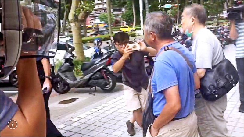 鄭(灰衣者)在友人陪同下離開警局。(記者邱俊福翻攝)