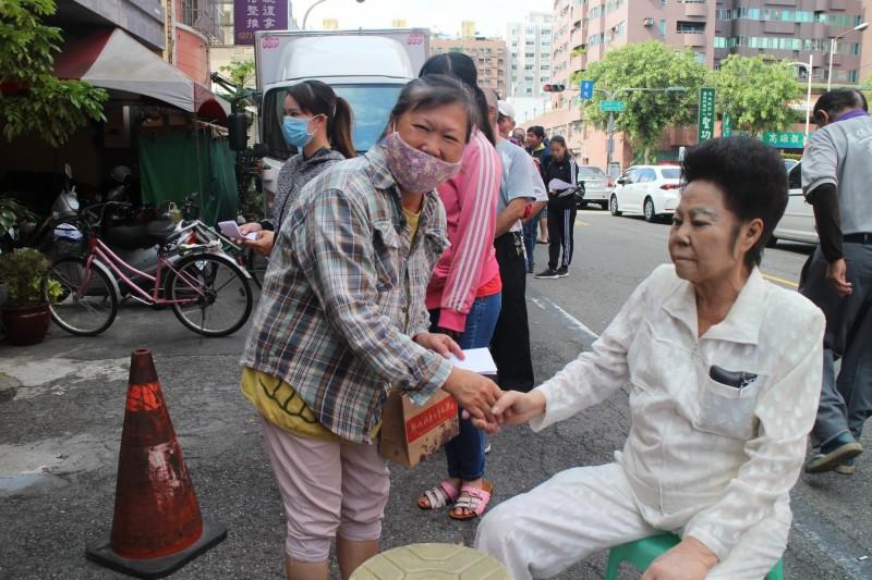 劉美枝(右)今身體不適,仍在家門口等候領取慰助金的中低收入戶。(記者方志賢翻攝)