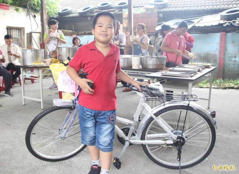小二生洪嘉駿大方捐出日前抽中的全新腳踏車,進行義賣,為食物銀行添購更多食品。(記者陳冠備攝)