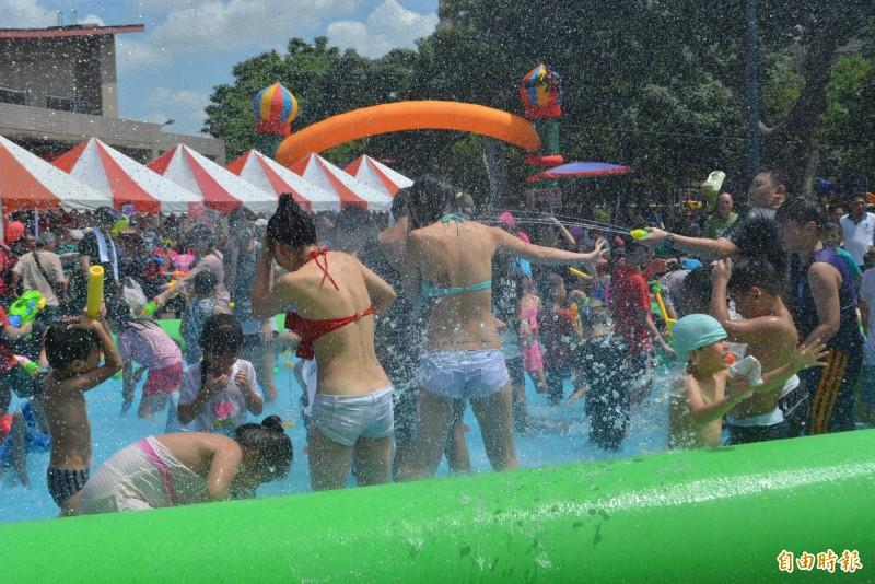 「大里人潑水節」今天登場,吸引上千位民眾到場玩水,穿著清涼的辣妹下水和民眾同樂,遭水槍猛攻。(記者陳建志攝)