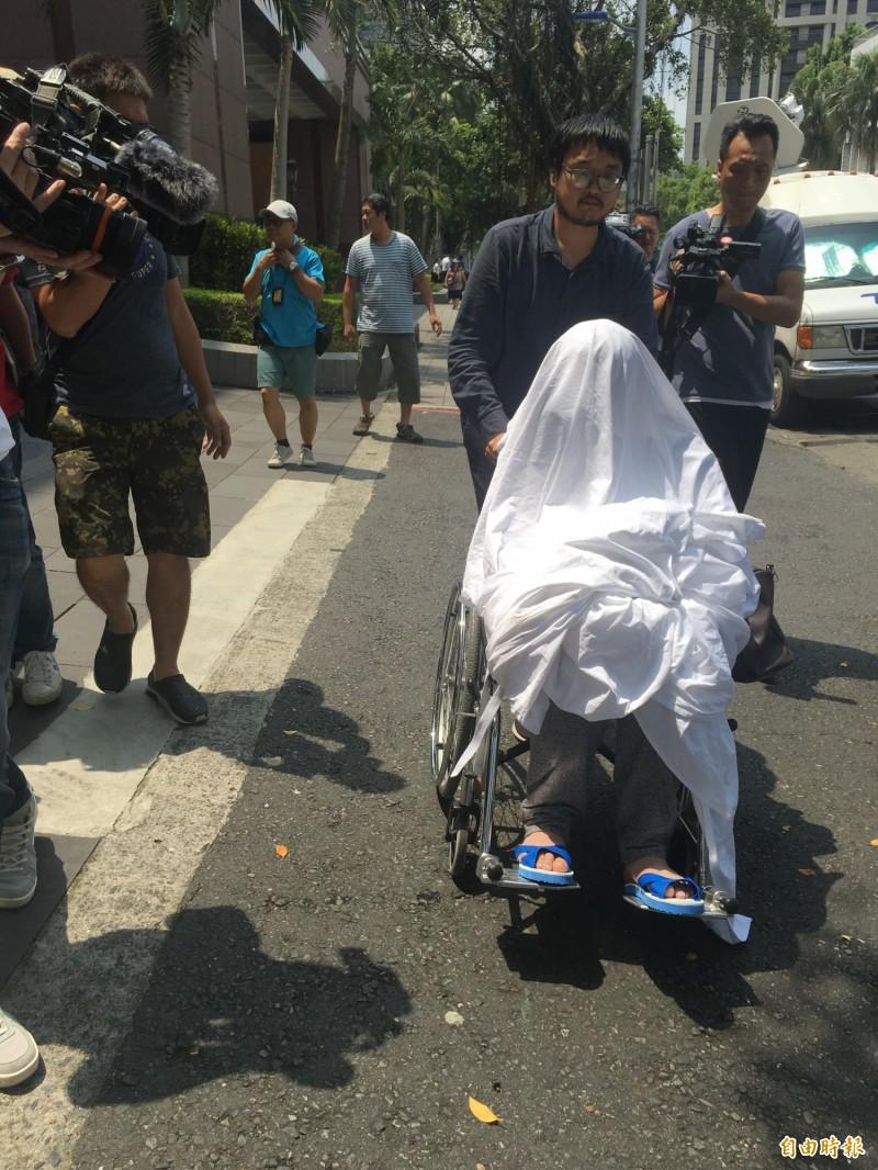 黃琪全身蓋白布坐輪椅,由律師郭上維推出法院。(記者張文川攝)