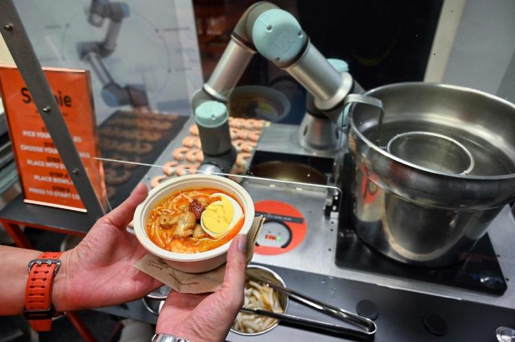機器人索菲可以在45秒內煮好1碗「叻沙海鮮湯麵」,讓不少試吃者嘖嘖稱奇。(法新社)