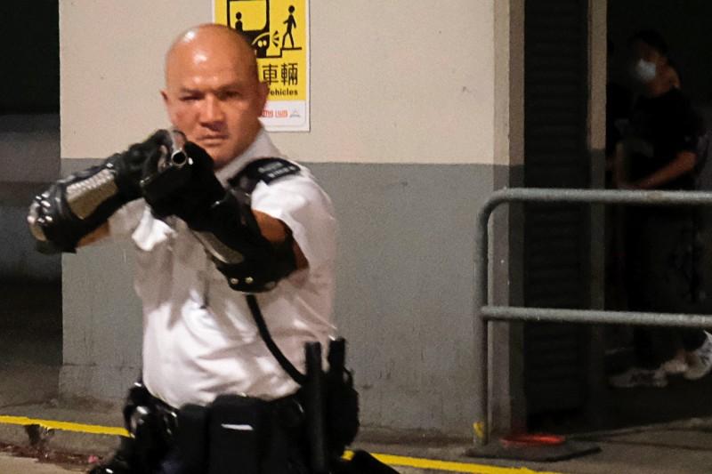 一名警察拿槍指向民眾。(路透)