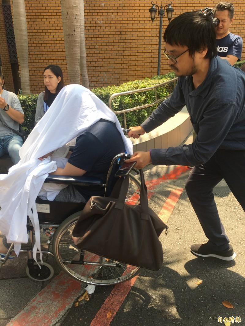 黃琪全身蓋白布坐輪椅,由律師推出法院。(資料照)