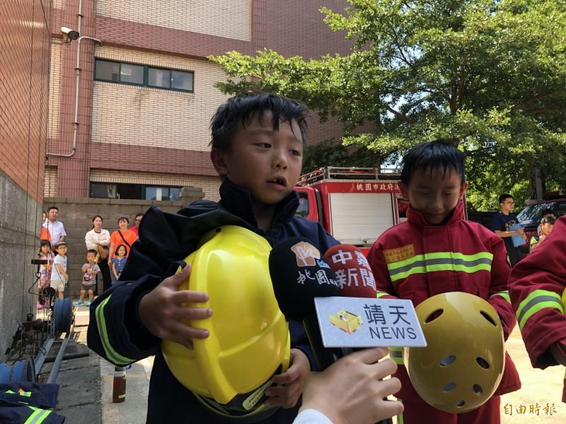 今天參與活動的小朋友童言童語的說,穿著消防衣很熱,消防員很辛苦,以後不當消防員。(記者魏瑾筠攝)