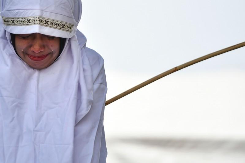印尼保守的亞齊省實施伊斯蘭律法,實施極具爭議的鞭刑,今(1)日有11名男女遭鞭打,其中一名19歲女子在行刑官動手後直接淚灑刑場。(法新社)