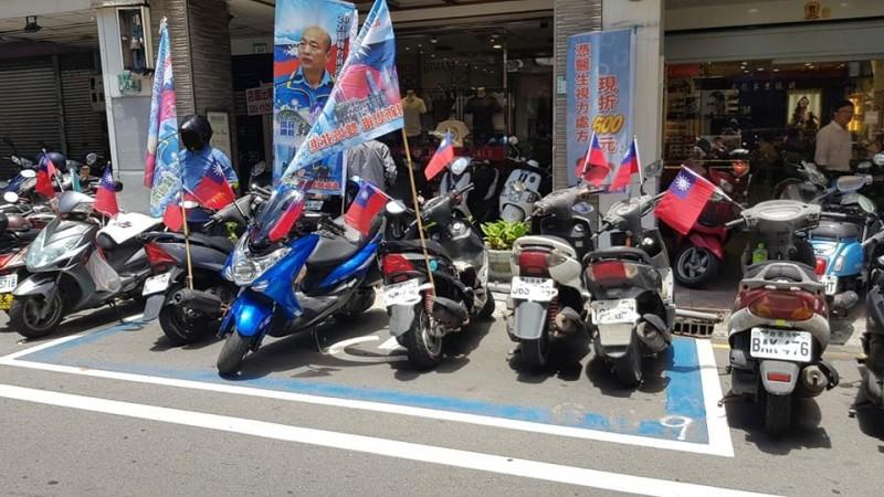 數台插滿韓國瑜旗幟與國旗的機車,停靠在殘障人士專屬汽車停車格中。(擷取自爆料公社)