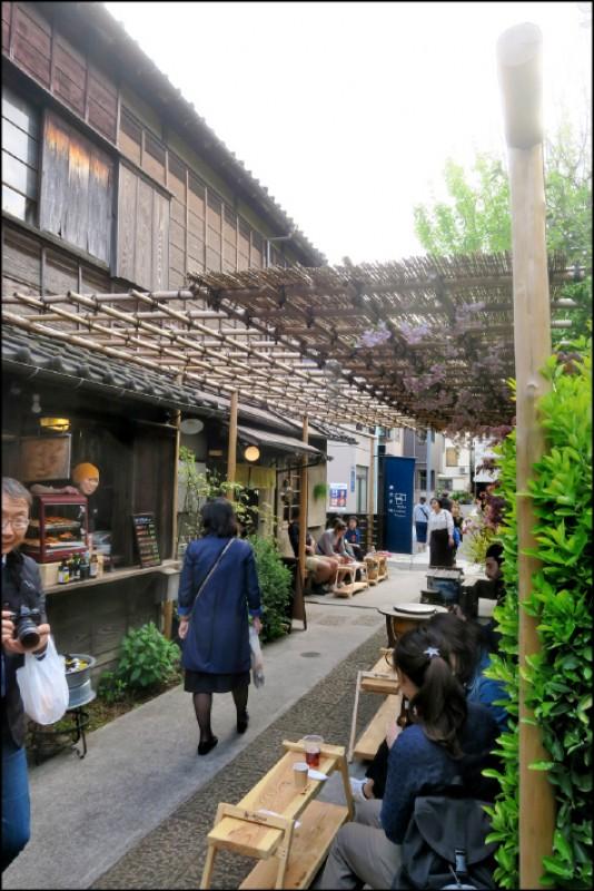 上野櫻木ATARI的戶外空間,設計了簡單的桌椅,人們可以買飲料與小吃在戶外享用,感受古意氛圍。(記者吳書緯/攝影)