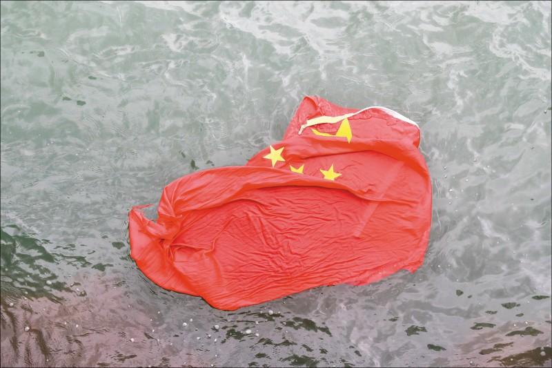 「旺角再遊行」3日下午登場,部份民眾拆下海港城購物中心5面中國國旗並將其丟入海中。(美聯社)