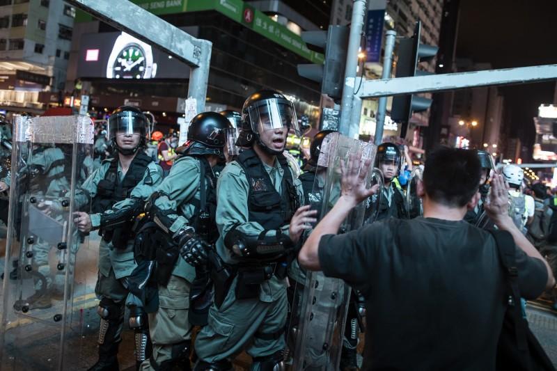 警察公共關係科高級警司余鎧均稱驅散行動「克制、忍讓」,示威行動危害居民安全,故警方以最低武力驅散。(彭博社)