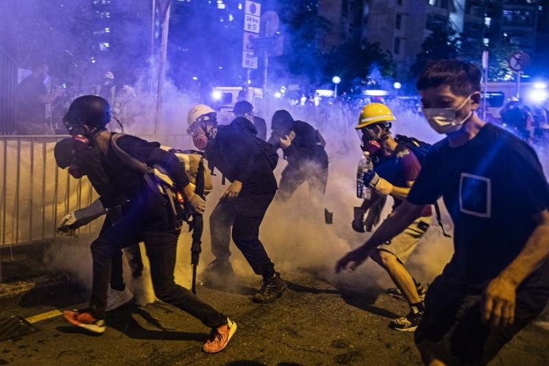 香港反送中運動在華人社會獲得的回響各不相同,作家顏擇雅發現,台灣多數人都報以同情,但不少住在西方國家的中國移民卻把這當成是「不願面對中國崛起」,新加坡、馬來西亞的華人更普遍站在支持香港政府那邊。圖為4日凌晨香港黃大仙一帶抗議群眾面對警方催淚瓦斯驅散。(彭博)