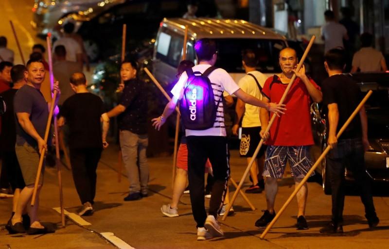 北角有多名男子持棍及籐條等武器的男子聚集。(路透)