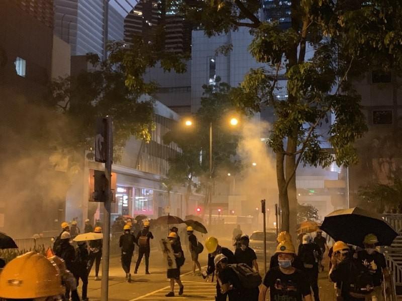 警方在警察總部週邊施放催淚彈。(圖擷取自Telegram_《背水目測》—港島台)