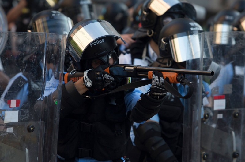 香港今(5)日舉行「大三罷」行動。圖中,警方正試圖驅離示威者,有鎮暴警察使用槍枝瞄準示威者。(法新社)