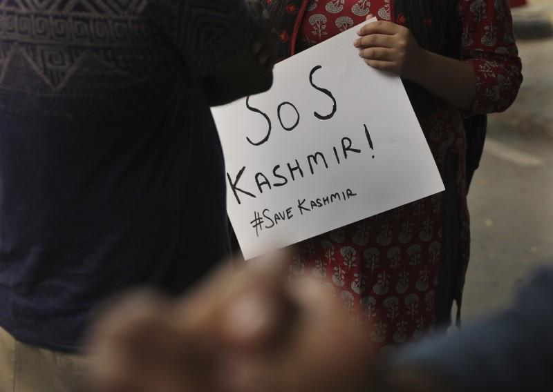 一名學生舉著「拯救喀什米爾」標語,反對印度國會的決定。(美聯社)