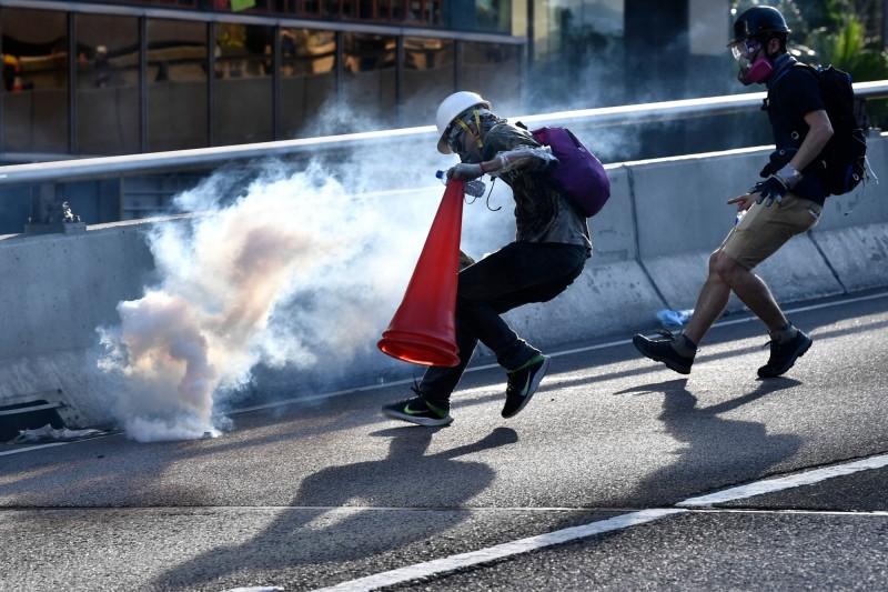 示威者拿著三角錐、水瓶,打算撲滅催淚彈。(法新社)